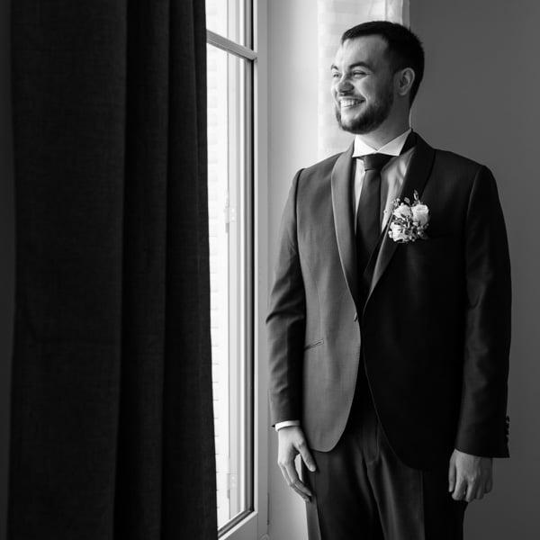 marié dans son costume regardant par la fenetre